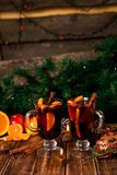 Mulled wine with fruits and spices on wooden table. Christmas decorations in background.  Winter warming drink with recipe ingredi. Mulled wine with fruits and Royalty Free Stock Photo