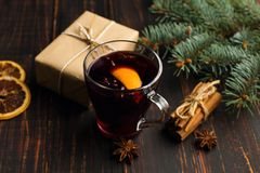Mulled wine, gift and spices on the table next to the tree. The concept of Christmas and New Year, decor. stock photos