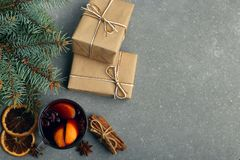 Mulled wine, a gift and spices on the table next to the tree. The concept of Christmas and New Year, decor. stock images