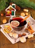 Mulled wine in glass with cinnamon stick, candle and sweets Stock Photo