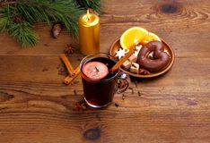 Mulled wine in glass with cinnamon stick, candle and sweets Stock Photos