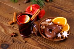 Mulled wine in glass with cinnamon stick, candle and sweets Royalty Free Stock Image