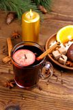 Mulled wine in glass with cinnamon stick, candle and sweets Stock Photography