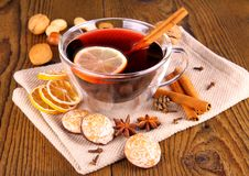 Mulled wine in glass with cinnamon stick, gingerbread and nuts Stock Photo