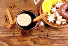 Mulled wine in glass with cinnamon stick and sweets Stock Photo