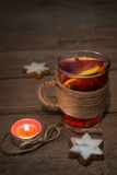 Mulled wine in a glass cup and a burning candle, text space Royalty Free Stock Photos
