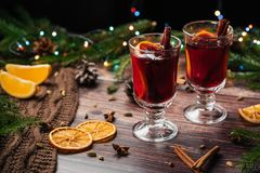 Mulled wine in glass glasses with orange slices, cinnamon sticks and spices with Christmas decor stock image