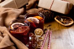 Mulled wine in glass mug with spices. Christmas hot drink on wooden table with craft presents stock images