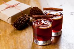 Mulled wine in glass mug with spices. Christmas hot drink on wooden table with craft presents stock photos