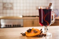 Mulled wine in glass with spice and fruit on wooden table in the kitchen. Copyspace royalty free stock photos