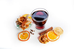Mulled wine in a glass with spices, ginger, cinnamon and fruit on a white background Royalty Free Stock Images