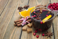 Mulled wine. Glass of mulled wine with spices on a wooden background royalty free stock photography