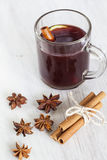 Mulled wine. Glass with mulled wine on white wooden Stock Images