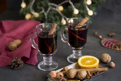 Mulled wine in glasses at black background. Fir wreath, lights, tray with orange, cinnamon, nuts, cone, spices. Winter composition. Mulled wine in glasses at royalty free stock photos