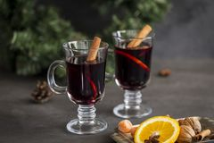 Mulled wine in glasses at black background. Fir wreath, tray with orange, cinnamon, nuts, cone and spices near stock photos