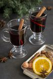 Mulled wine in glasses at black background. Fir wreath, tray with orange, cinnamon, nuts, cone and spices near. Winter composition. Mulled wine in glasses at stock photo