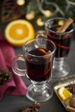 Mulled wine in glasses at black background. Fir wreath, tray with orange, cinnamon, nuts, cone and spices near royalty free stock image