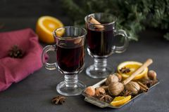 Mulled wine in glasses at black background. Fir wreath, tray with orange, cinnamon, nuts, cone and spices near. Winter composition. Mulled wine in glasses at royalty free stock photo