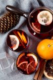Mulled wine in glasses with orange and spices with grey scarf.  royalty free stock photography