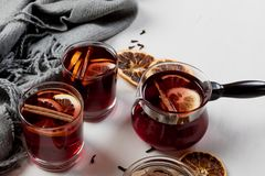 Mulled wine in glasses with orange and spices near gray scarf royalty free stock photography
