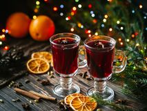 Mulled wine in glasses on the table decorated with a Christmas tree. Orange slices, anise stars, cardamom, cinnamon stock photo