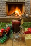Mulled wine glintwine in drinking glass and christmas decorations, against cozy fireplace background. Christmas drink. Cozy fireplace concept. Mulled wine and royalty free stock image
