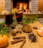 Mulled wine glintwine in drinking glasses and christmas decorations, against cozy fireplace background. Christmas drink. Cozy fireplace concept. Mulled wine royalty free stock photography