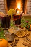 Mulled wine glintwine in drinking glasses and christmas decorations, against cozy fireplace background. Christmas drink. Cozy fireplace concept. Mulled wine stock photo