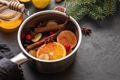 Mulled wine hot drink with citrus, apple and spices in aluminum casserole and Fir branch on background. Mulled wine hot drink with citrus, apple and spices in stock image