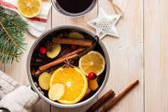 Mulled wine hot drink with citrus, apple and spices in aluminum casserole and Fir branch on background. Mulled wine hot drink with citrus, apple and spices in stock photos