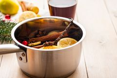 Mulled wine hot drink with citrus, apple and spices in aluminum casserole and Fir branch on background. Mulled wine hot drink with citrus, apple and spices in royalty free stock image