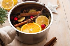 Mulled wine hot drink with citrus, apple and spices in aluminum casserole and Fir branch on background. Mulled wine hot drink with citrus, apple and spices in royalty free stock photos