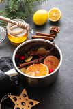 Mulled wine hot drink with citrus, apple and spices in aluminum casserole and Fir branch on background. Mulled wine hot drink with citrus, apple and spices in stock photo