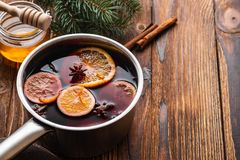 Mulled wine hot drink with citrus, apple and spices in aluminum casserole and Fir branch on background. Mulled wine hot drink with citrus, apple and spices in stock photography