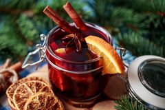 Mulled wine i ett exponeringsglas Varmt funderat vin för jul i ett exponeringsglas med kryddor och citrusfrukt Funderat vin med k Arkivfoton