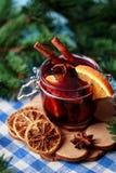 Mulled wine i ett exponeringsglas Varmt funderat vin för jul i ett exponeringsglas med kryddor och citrusfrukt Funderat vin med k Arkivfoto