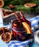 Mulled wine i ett exponeringsglas Varmt funderat vin för jul i ett exponeringsglas med kryddor och citrusfrukt Funderat vin med k Royaltyfri Bild