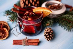 Mulled wine i ett exponeringsglas Varmt funderat vin för jul i ett exponeringsglas med kryddor och citrusfrukt Funderat vin med k Arkivbild
