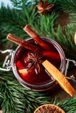 Mulled wine i ett exponeringsglas Varmt funderat vin för jul i ett exponeringsglas med kryddor och citrusfrukt Funderat vin med k Fotografering för Bildbyråer