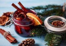 Mulled wine i ett exponeringsglas Varmt funderat vin för jul i ett exponeringsglas med kryddor och citrusfrukt Funderat vin med k Royaltyfria Bilder
