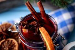 Mulled wine i ett exponeringsglas Varmt funderat vin för jul i ett exponeringsglas med kryddor och citrusfrukt Funderat vin med k Royaltyfri Foto