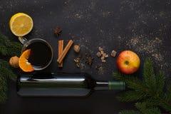 Mulled wine ingredients. Christmas Mulled wine recipe ingredients on black. Bottle of wine, orange, apple, lemon, cinnamon sticks, anise, nutmeg, cloves and Royalty Free Stock Images