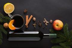 Mulled wine ingredients. Christmas Mulled wine recipe ingredients on black. Bottle of wine, orange, apple, lemon, cinnamon sticks, anise, nutmeg, cloves and Stock Photography