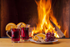 Mulled wine and ingredients at fireplace Stock Images