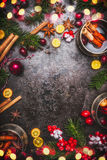 Mulled wine and ingredients spices with fir branches and Christmas decoration and bokeh on dark rustic background, top view Stock Images