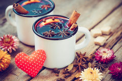 Mulled wine in mugs, red heart, spice and dry flowers. Stock Image
