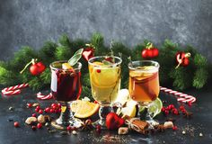 Mulled wine and mulled cider. Hot winter drinks and cocktails for christmas or new year`s eve in glass mugs with spices and citru. S fruit