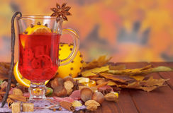 Mulled wine, nuts and sweets on background of autumn leaves. Royalty Free Stock Photography