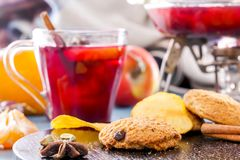 Mulled wine with oatmeal cookies, cornflakes, fruit and spices. Fruit tea. Punch, grog. Hot winter wine Royalty Free Stock Photo