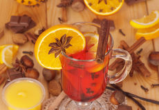 Mulled wine, orange, honey, nuts and sweets on light wood. Stock Images